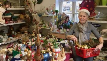FAIRKAUF-Laden-Mitarbeiterin Gabi Stölting befüllt beispielhaft einen Einkaufskorb mit Advents- und Weihnachtsartikeln. | Foto: Jacobi / Caritas Südniedersachsen